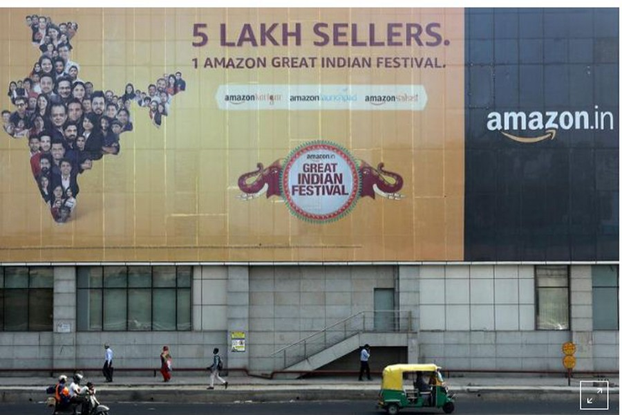 FILE PHOTO: People move past a hoarding of Amazon India outside a metro rail station in New Delhi, India, October 23, 2019. REUTERS/Anushree Fadnavis