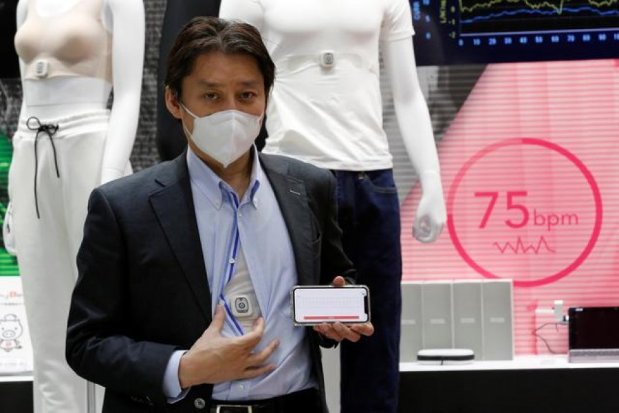 Toyobo's staff shows the 'COCOMI' clothing, which can acquire physiological information data, and a smartphone displaying the measured heart rate during its demonstration at the Wearable Expo in Tokyo, Japan, January 20, 2021. REUTERS/Kim Kyung-Hoon
