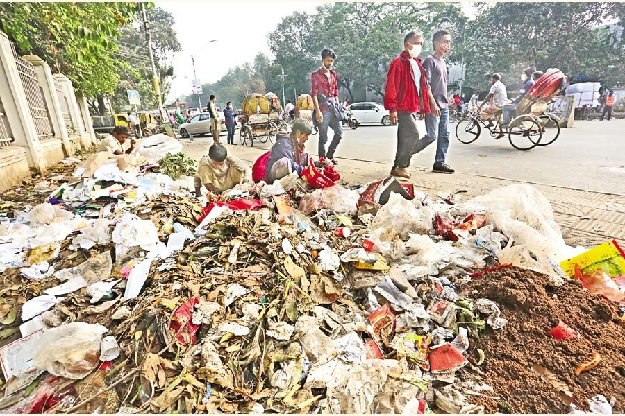 Pedestrians walk past a heap of garbage in the city's Dhaka Medical College and Hospital area on Friday — FE photo