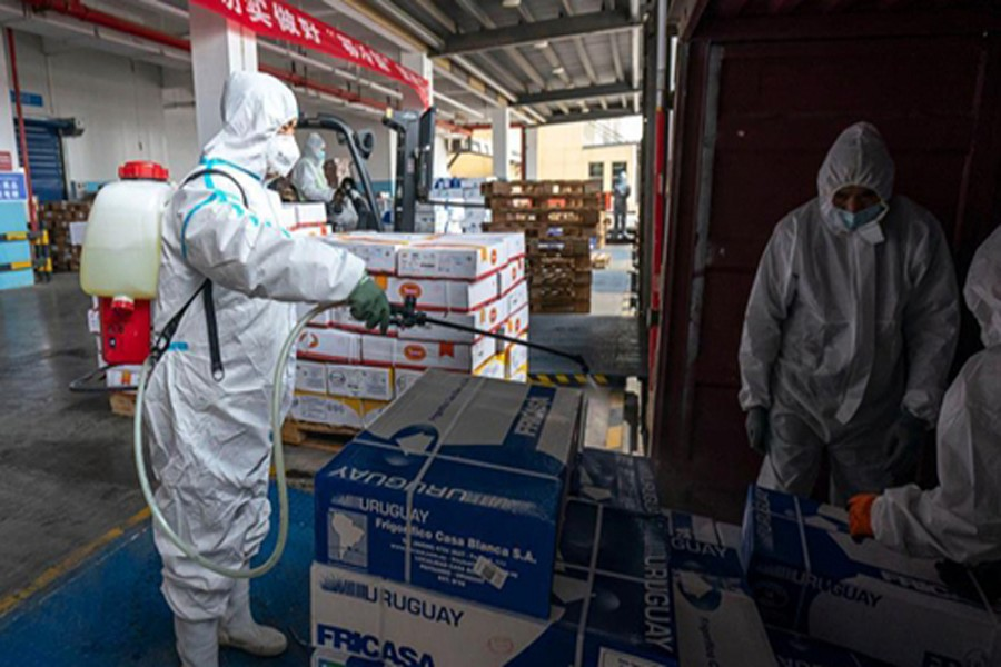 A staff member sprays disinfectant on the package of imported cold chain food at a regional cold chain centre in Wuhan, capital of central China's Hubei Province, Jan 07, 2021.Photo: Xinhua