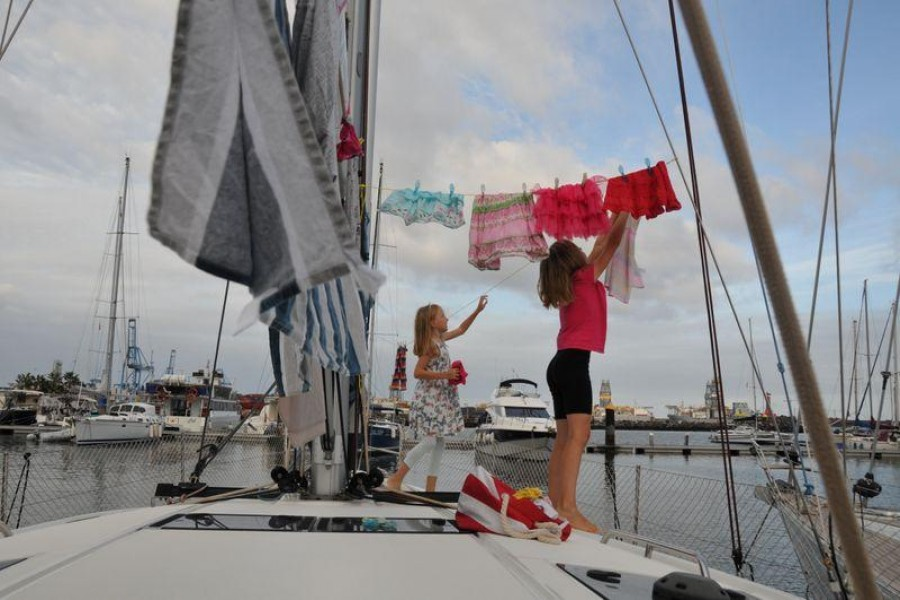 Katalin Bosze and Boroka Bosze hang clothes to dry on the sailing boat 'Teatime' in Las Palmas, Spain on October 5, 2020 — Sailingteatime via Reuters