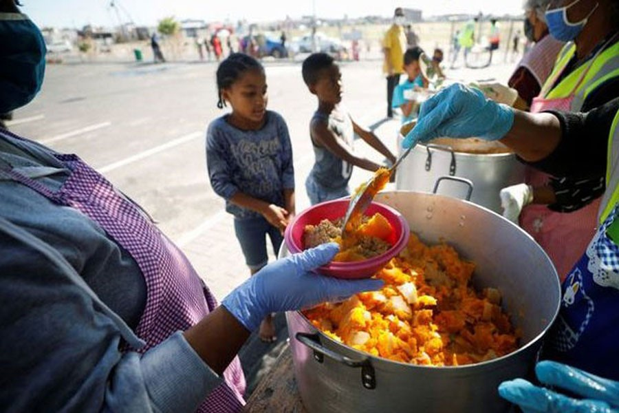 Children queue for food at a school feeding scheme during a nationwide lockdown aimed at limiting the spread of the coronavirus disease (COVID-19) in Blue Downs township near Cape Town, South Africa, May 4, 2020. REUTERS