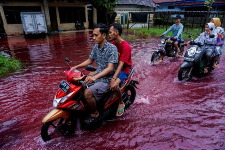 People ride motorbikes through a flooded road with red water due to the dye-waste from cloth factories, in Pekalongan, Central Java province, Indonesia on February 6, 2021 — Antara Foto via Reuters