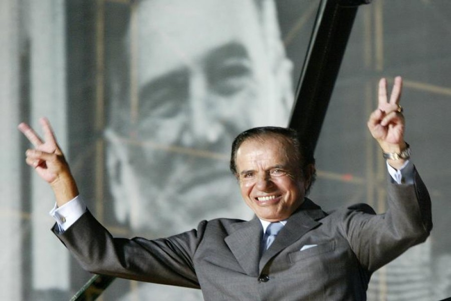 FILE PHOTO: Argentine presidential candidate Carlos Menem stands in front of a giant poster of former President Juan Domingo Peron, as he waves to thousands of followers in River Plate Stadium during the final rally of his campaign, in Buenos Aires, April 24, 2003. REUTERS/Rickey Rogers/File Photo