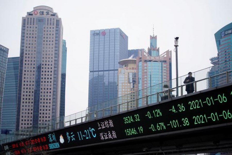 A man stands on an overpass with an electronic board showing Shanghai and Shenzhen stock indexes, at the Lujiazui financial district in Shanghai, China, January 6, 2021 — Reuters/Files