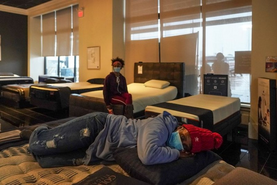 Tiffany Woodley, front, rests on a bed while taking a shelter at Gallery Furniture store which opened its door and transformed into a warming station after winter weather caused electricity blackouts in Houston, Texas, US, February 17, 2021 — Reuters