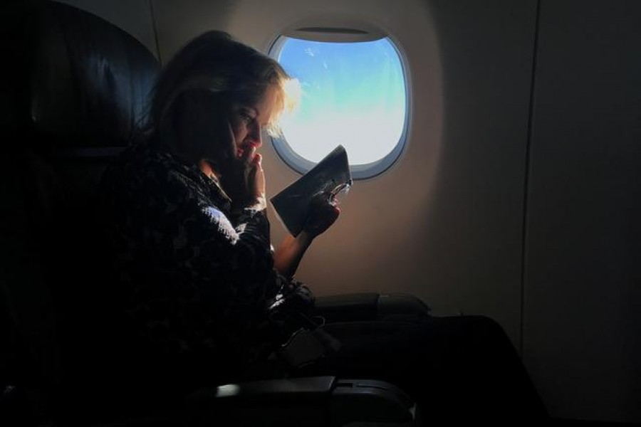 A woman reads while sitting in a business class seat on a flight from New York City to Washington D.C. U.S., December 7, 2017. REUTERS/Carlo Allegri/File Photo