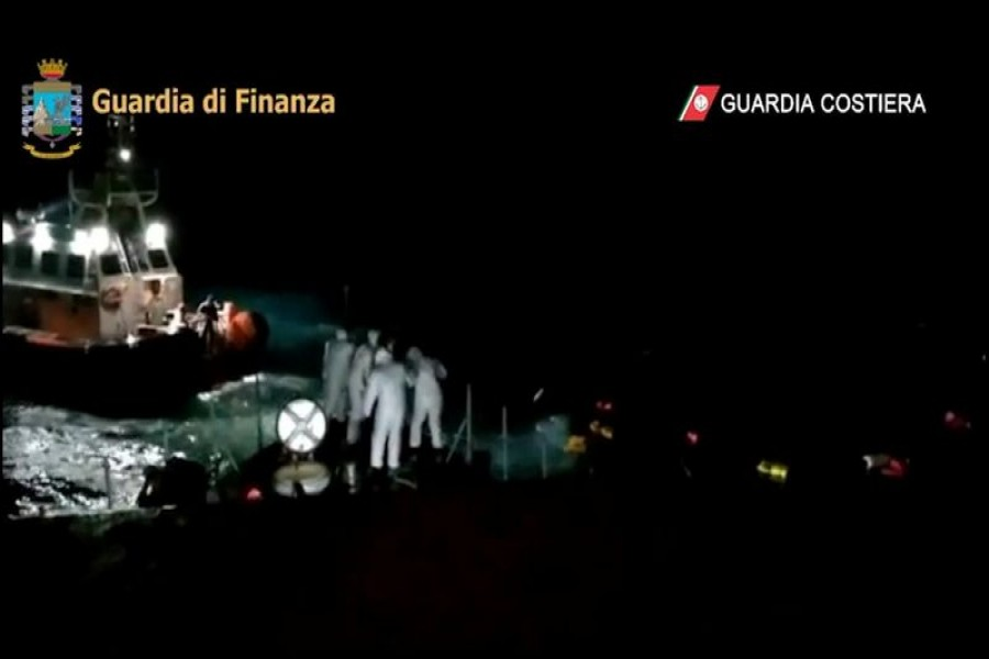 Members of the Italian Coast Guard throw buoyancy aid during a rescue operation after a boat carrying migrants capsized off the coast of Lampedusa, Italy, February 20, 2021 in this still image taken from video. Guardia Costiera/Handout via REUTERS