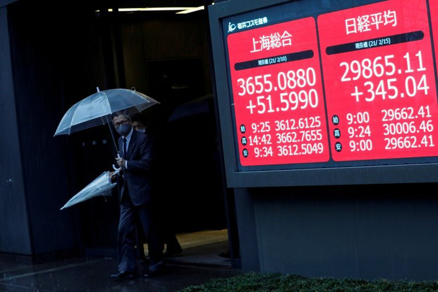 Men holding umbrellas walk near an electric board showing Nikkei index at a brokerage in Tokyo, Japan on February 15, 2021 — Reuters photo