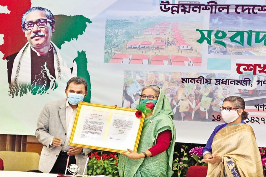 Prime Minister Sheikh Hasina receiving the final recommendation of the UN Committee for Development Policy on its graduation from the LDC category from Finance Minister AHM Mustafa Kamal at a media briefing on Saturday — PID