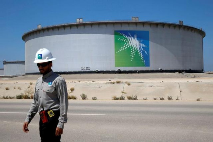 FILE PHOTO: An Aramco employee walks near an oil tank at Saudi Aramco's Ras Tanura oil refinery and oil terminal in Saudi Arabia May 21, 2018. REUTERS/Ahmed Jadallah/File Photo