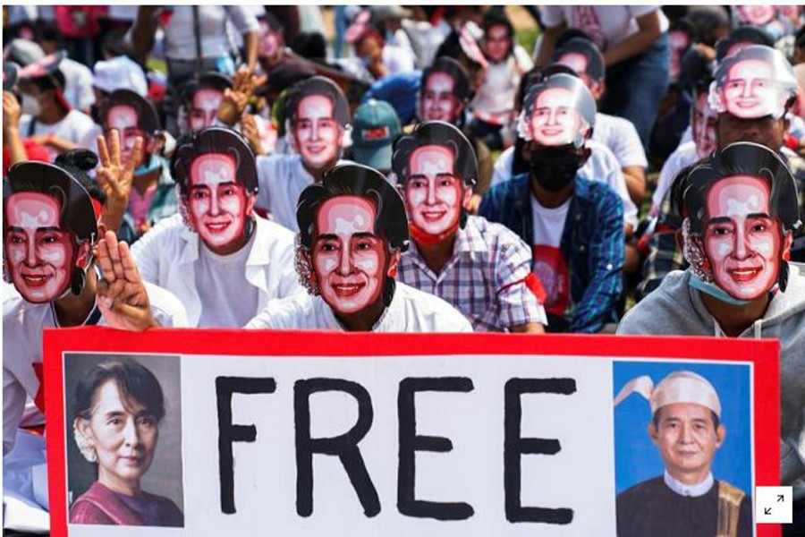 FILE PHOTO: Protesters wearing masks depicting ousted leader Aung San Suu Kyi, flash three-finger salutes as they take part in a protest against the military coup in Yangon, Myanmar, February 28, 2021. REUTERS/Stringer