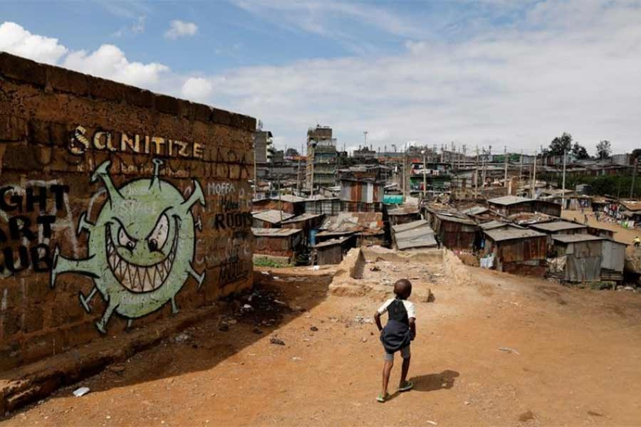 A boy walks in front of graffiti promoting the fight against the coronavirus disease (COVID-19) in the Mathare slums of Nairobi of Kenya last year -Reuters file photo