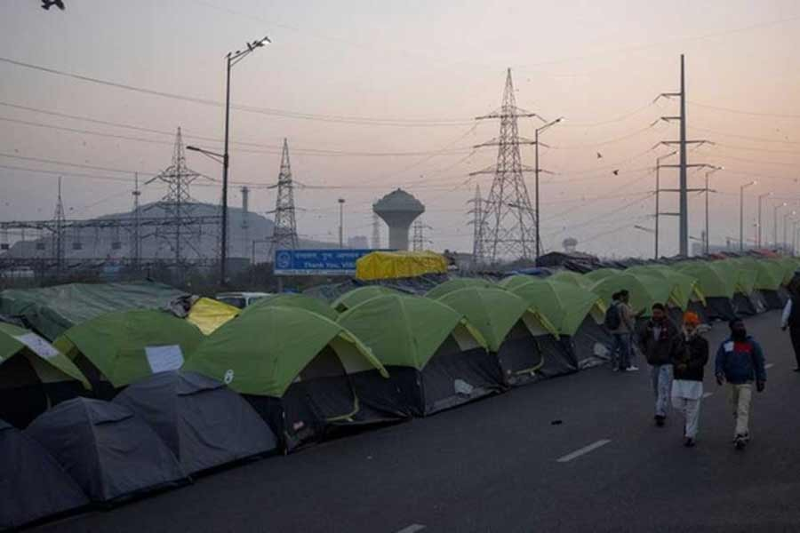 Farmers walk outside their tents at the site of a protest against new farm laws, at the Delhi-Uttar Pradesh border in Ghaziabad of India in January –Reuters file photo