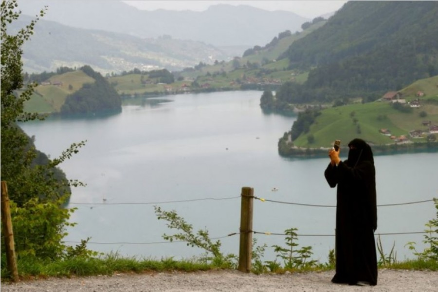 A woman wearing a niqab takes a picture from a lookout above lake Lungenersee at the Bruenigpass mountain pass road, Switzerland August 3, 2017. On March 7 Switzerland's voters will decide about a nationwide veil ban. REUTERS