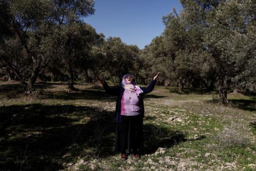 Tayyibe Demirel, 64, who is refusing to sell her olive grove to coal mining companies, prays as she stands in her olive grove in Turgut village near southwestern town of Yatagan in Mugla province, Turkey, February 24, 2021 — Reuters