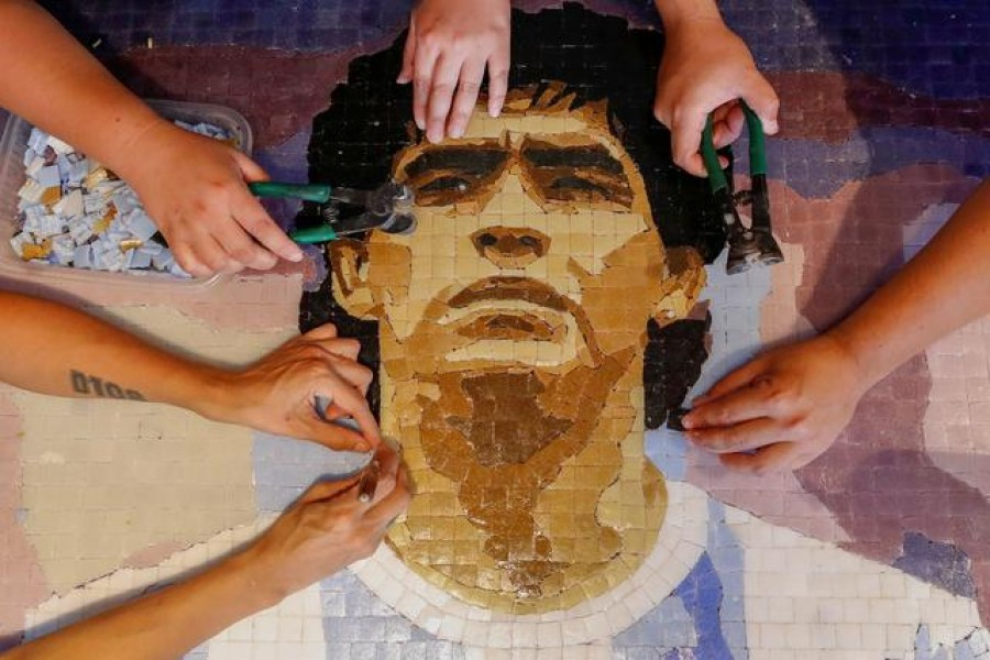FILE PHOTO: Gabriela Pereyra, Paula Soto, ad Gonzalo Lopez Lluch, members of the cultural organisation Comando Maradona, prepare a mosaic as a homage to late Argentine soccer superstar Diego Armado Maradona, at their workshop, in Buenos Aires, Argentina February 24, 2021. Picture taken February 24, 2021. REUTERS/Agustin Marcarian