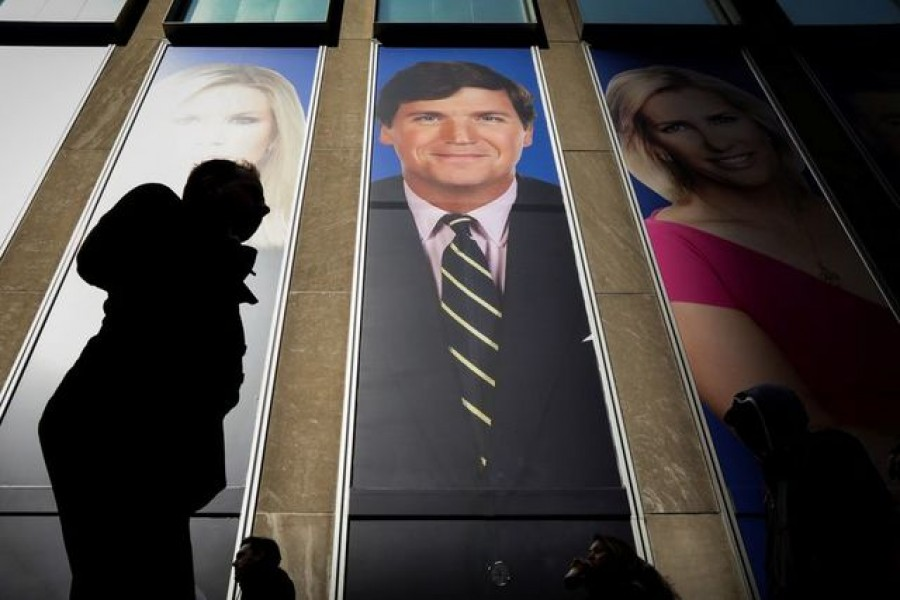 People pass by a promo of Fox News host Tucker Carlson on the News Corporation building in New York, US, March 13, 2019 — Reuters