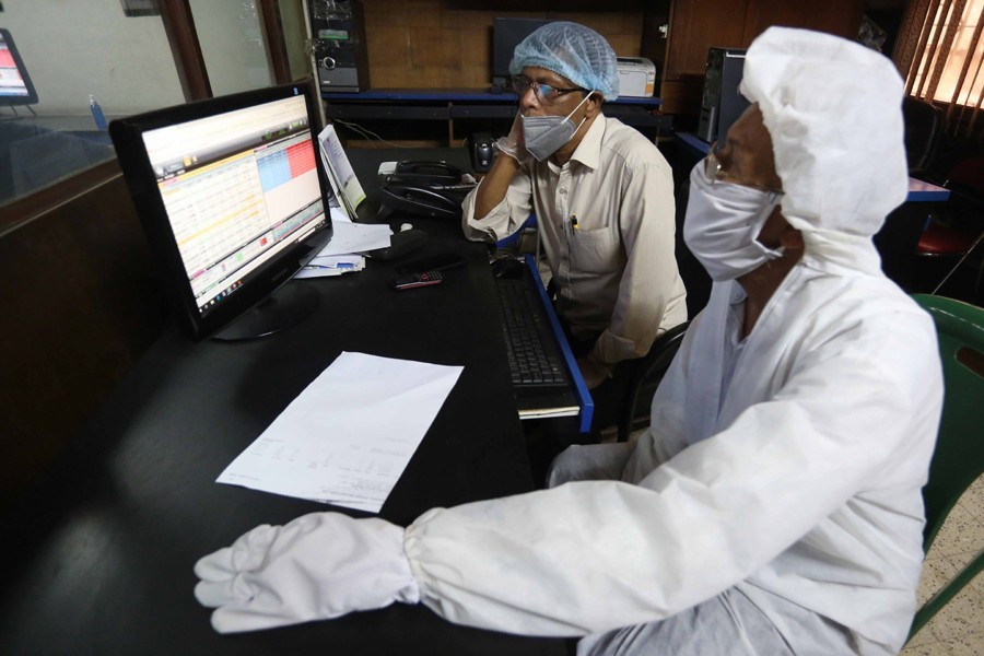 Investors, in protective suits, monitoring stock price movements on computer screens at a brokerage house in the capital city — FE/Files