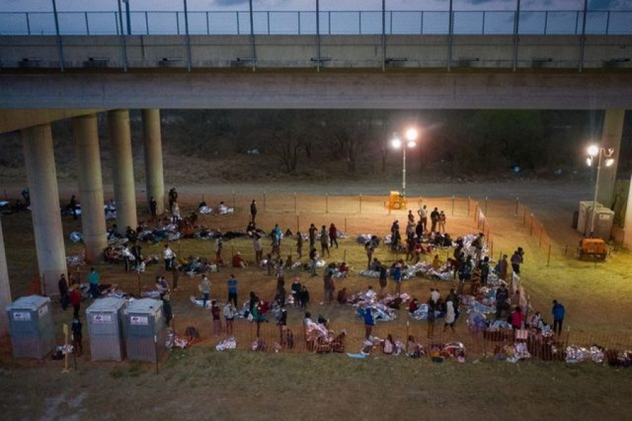Asylum seeking migrant families and unaccompanied minors from Central America take refuge in a makeshift U.S. Customs and Border Protection processing center under the Anzalduas International Bridge after crossing the Rio Grande river into the United States from Mexico in Granjeno, Texas, U.S., March 12, 2021. REUTERS/Adrees Latif