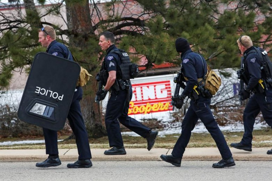 Law enforcement officers sweep the parking lot at the site of a shooting at a King Soopers grocery store in Boulder, Colorado, U.S. March 22, 2021. REUTERS/Kevin Mohatt