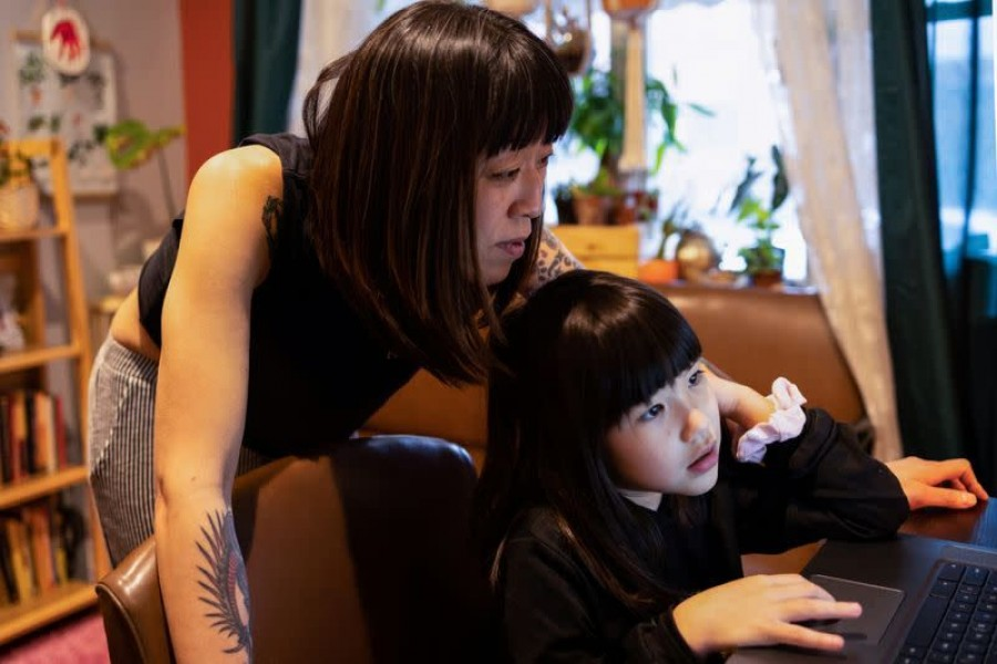 Stefany Stuber, 40, a Korean-American who speaks with her daughter Olivia Metzler, 7, about recent attacks on Asian Americans, shops for clothes for her daughter on the computer in Philadelphia, Pennsylvania, US on March 24, 2021 — Reuters photo