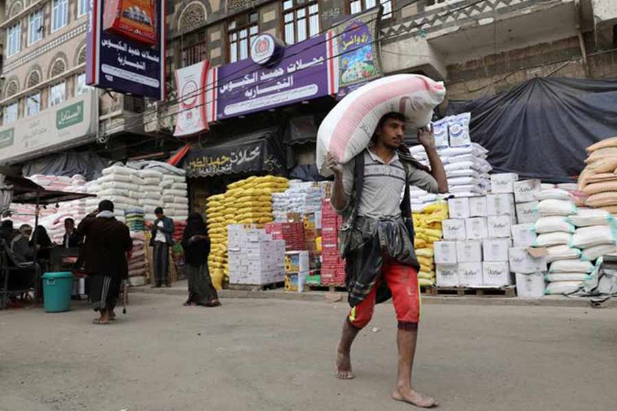 A worker carrying a sack of wheat flour outside a food store amid concerns over the spread of the COVID-19 in Sanaa of Yemen last year –Reuters file photo