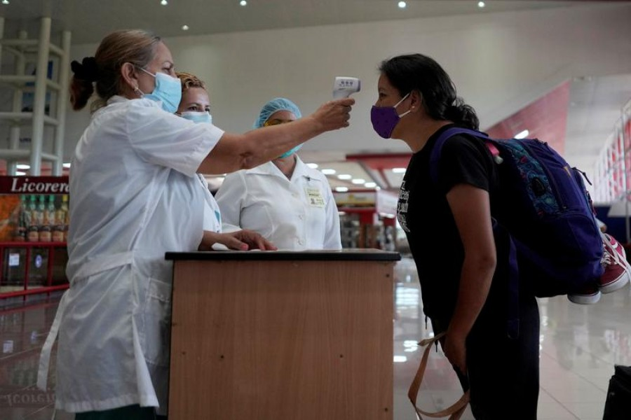 FILE PHOTO: A traveller has her temperature checked at the Jose Marti International Airport amid concerns about the spread of the coronavirus disease (COVID-19), in Havana, Cuba, November 15, 2020. REUTERS/Alexandre Meneghini