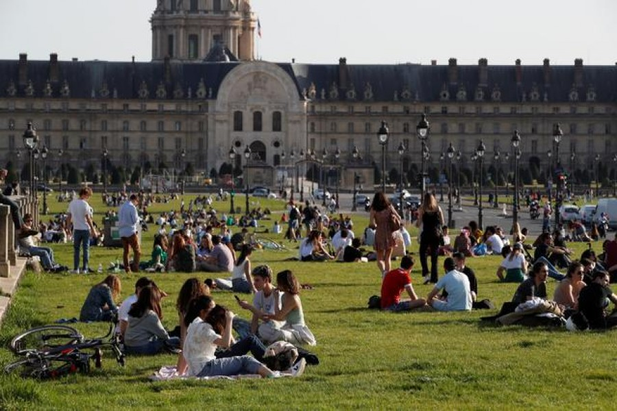 People enjoy a sunny and warm weather sitting on the grass near the Invalides in Paris amid the coronavirus disease (Covid-19) outbreak in France, March 31, 2021 — Reuters