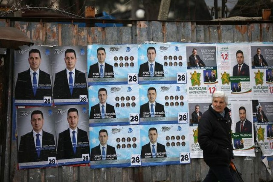 FILE PHOTO: A woman walks past election posters of the ruling centre-right GERB party in the town of Dupnitsa, Bulgaria, April 2, 2021. REUTERS/Stoyan Nenov