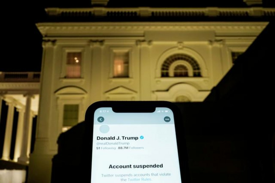FILE PHOTO: A photo illustration shows the suspended Twitter account of US President Donald Trump on a smartphone and the White House in Washington, US, January 8, 2021. REUTERS/Joshua Roberts/Illustration/File Photo