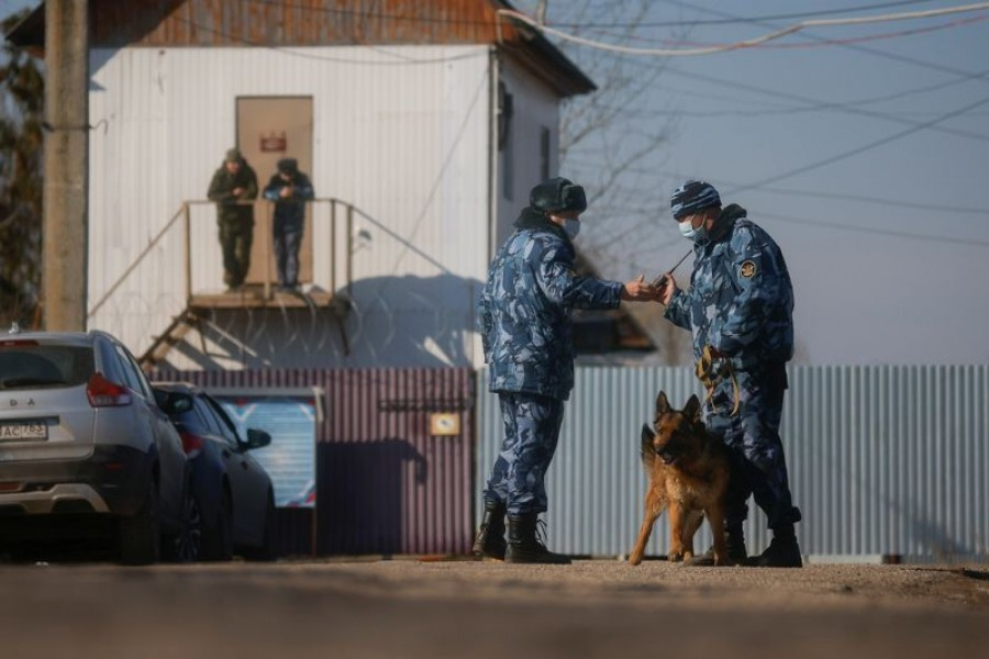 Law enforcement officers with a dog stand guard near a security checkpoint of the IK-2 corrective penal colony, where Kremlin critic Alexei Navalny serves his jail term, in the town of Pokrov, Russia April 6, 2021. REUTERS/Maxim Shemetov