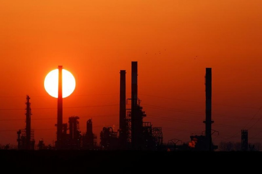 The sun sets behind the chimneys of the Total Grandpuits oil refinery, southeast of Paris, France, March 1, 2021 — Reuters/Files