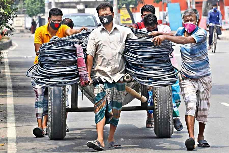 Labourers carrying iron rods by a push-cart, amid the coronavirus (Covid-19) outbreak, at Tejgaon in Dhaka city last year —FE file photo