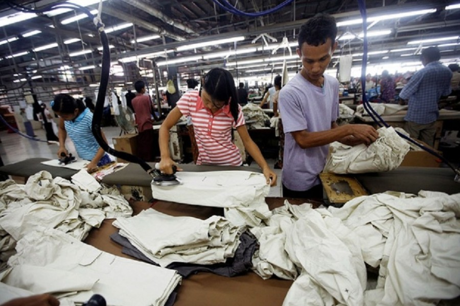 Workers iron and arrange clothing at a garment factory at Hlaing Taryar industrial zone in Yangon, March 10, 2010. Reuters