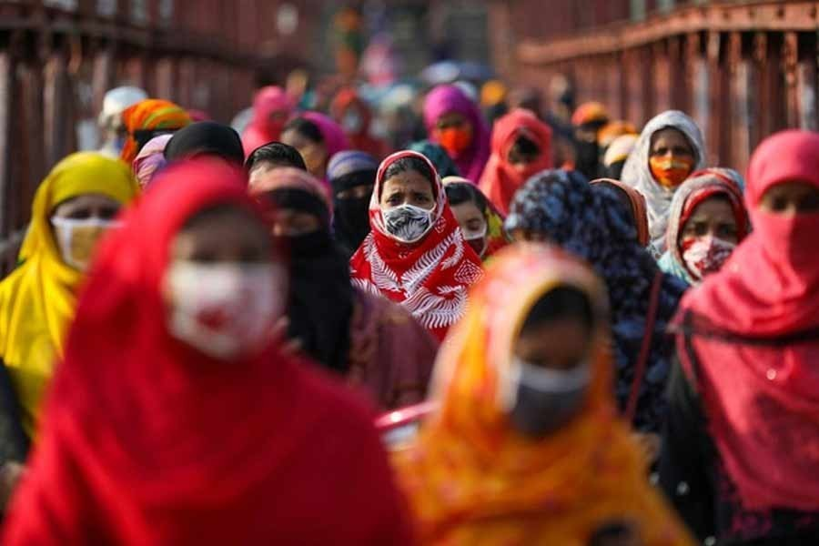 Garment workers returning from a workplace as factories reopened after the government has eased the restrictions amid concerns over the coronavirus disease (Covid-19) outbreak in Dhaka, May 04, 2020 – Reuters/Files