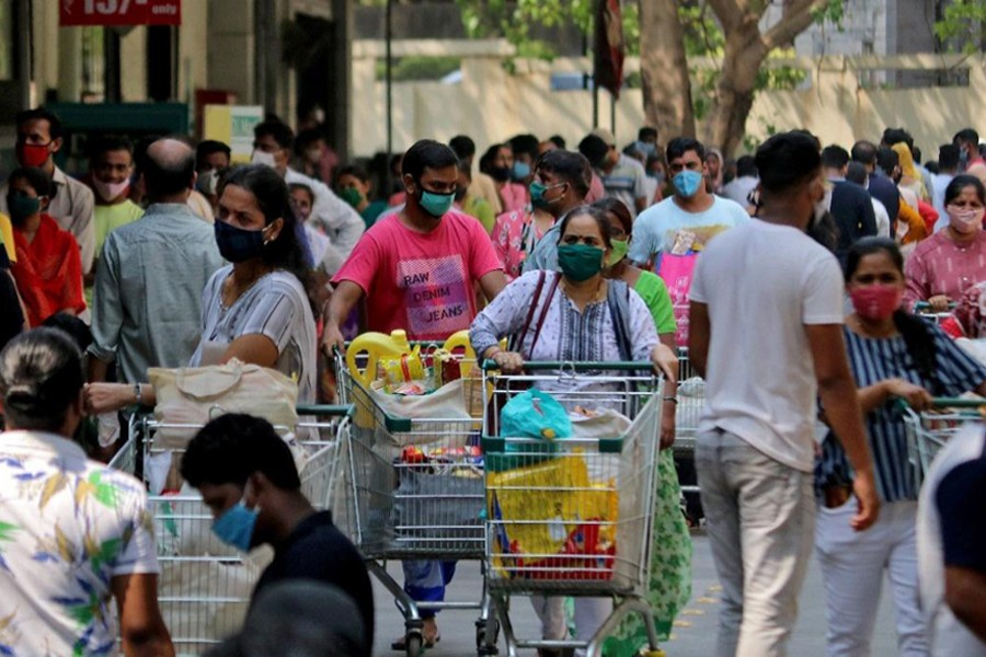 People push trolleys loaded with grocery items as others wait to enter a supermarket, amidst the spread of the coronavirus disease (Covid-19) in Mumbai, India on April 14, 2021 — Reuters photo