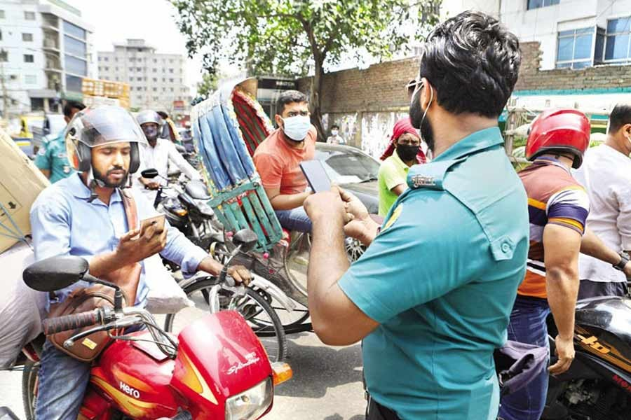 A policeman checks the movement pass on a mobile phone at Dayaganj in the city during lockdown on Thursday — FE photo