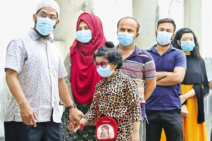 With the resurgence of coronavirus, more children are getting infected this time. The photo shows a little girl waiting in a queue at Bangabandhu Sheikh Mujib Medical University Hospital in the city recently to have her sample tested for the virus —FE file photo