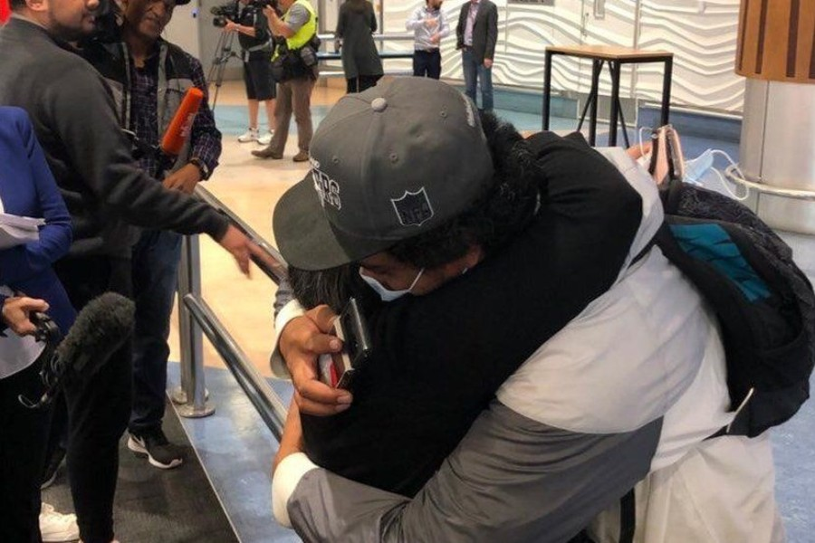 - Two people embrace at Auckland airport