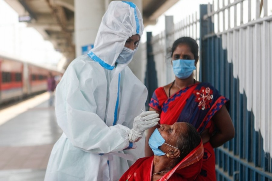A healthcare worker in personal protective equipment (PPE) collects a swab sample from a woman, amidst the spread of the coronavirus disease (Covid-19), at a railway station in Mumbai, India, April 16, 2021 — Reuters