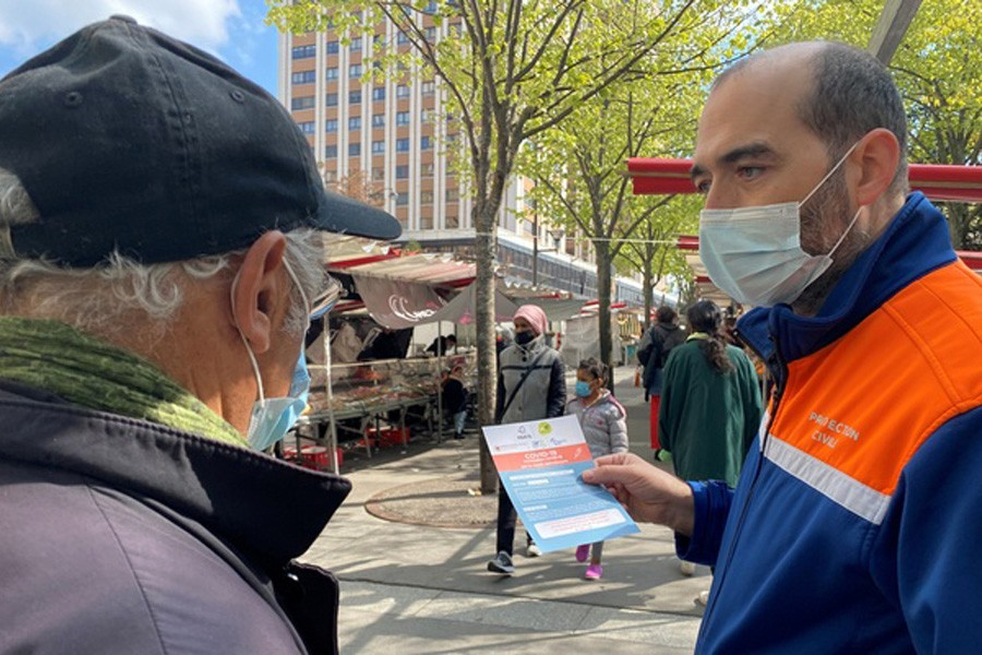 Volunteers from French Protection Civile association hand out leaflets at a fresh producer market to try to persuade Parisians over 55 to take AstraZeneca vaccine, amid the coronavirus disease (COVID-19) pandemic, in Paris, France, April 16, 2021. Reuters