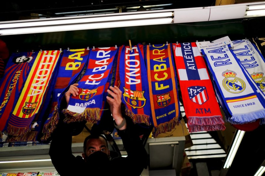 FC Barcelona, Atletico Madrid and Real Madrid scarves are displayed inside a store at Las Ramblas in Barcelona, Spain on April 19, 2021 — Reuters photro