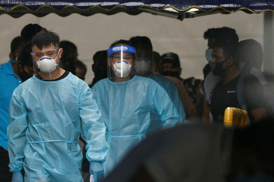 Personnel in protective garment usher a group of migrant workers to take a bus to a government quarantine facility after workers were tested positive for the coronavirus disease (Covid-19) at Westlite Woodlands dormitory in Singapore on April 22, 2021 — Reuters photo