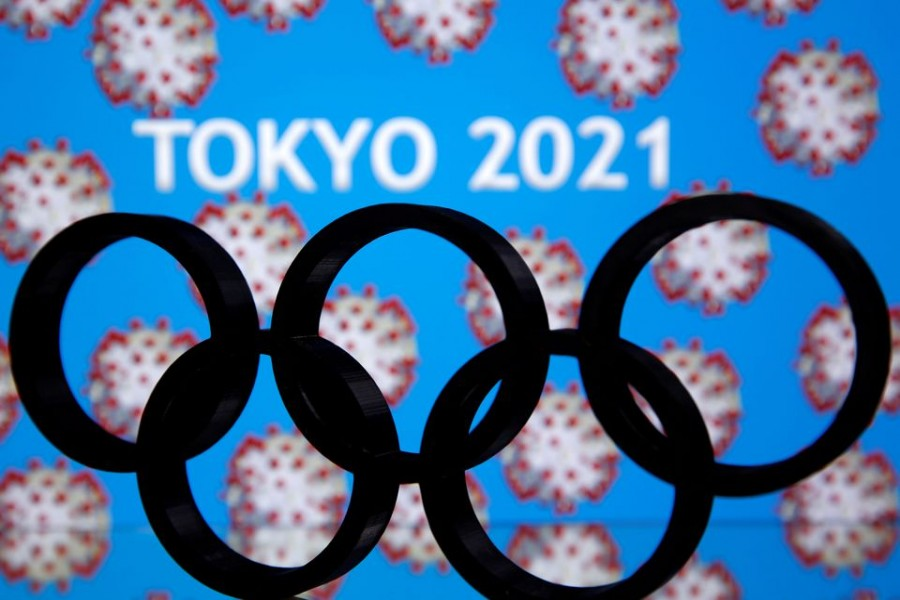 """A 3D printed Olympics logo is seen in front of displayed """"Tokyo 2021"""" words in this illustration taken March 24, 2020. REUTERS/Dado Ruvic TPX IMAGES OF THE DAY"""