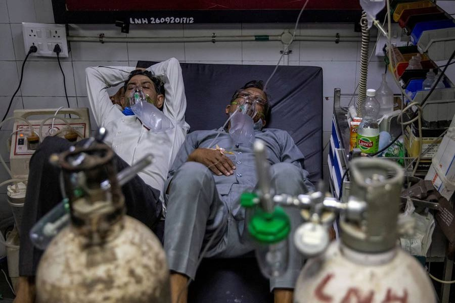 COVID-19 patients sharing a bed as they receive treatment at the casualty ward in Lok Nayak Jai Prakash (LNJP) hospital in New Delhi recently -Reuters file photo