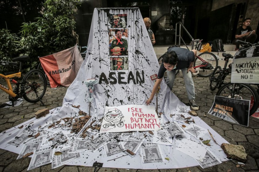 A woman prepares a placard out of crossed out portraits of Myanmar's junta chief Senior General Min Aung Hlaing during protest against the military coup in Myanmar, in Jakarta, Indonesia, April 24, 2021 in this photo taken by Antara Foto. Antara Foto/Dhemas Reviyanto/ via REUTERS