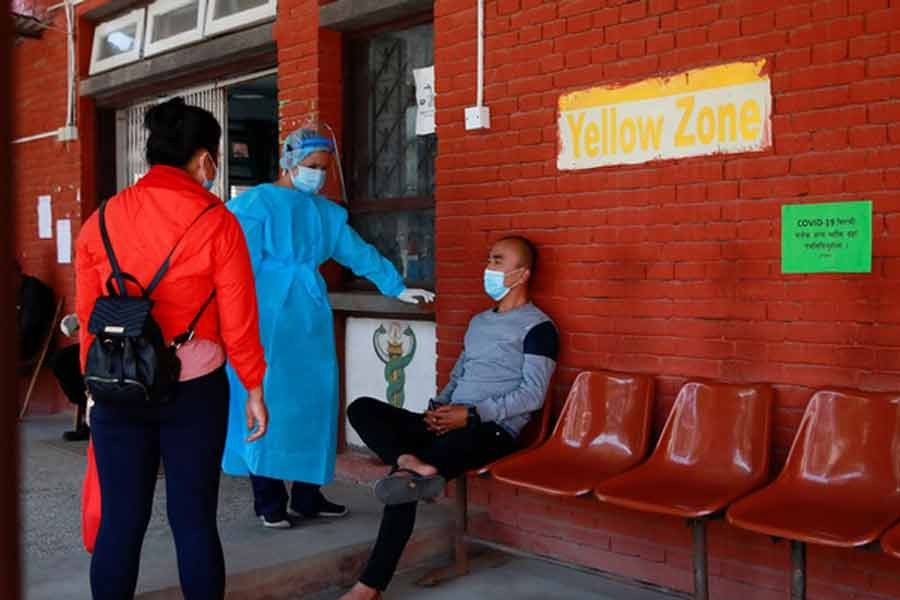 A health worker interrogating a patient (R) arriving with breathing difficulty at a hospital for treatment on Monday as the major second wave of coronavirus disease (COVID-19) surges in Nepal -Reuters photo