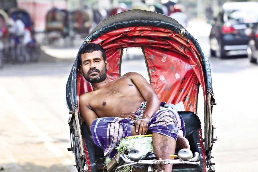 With a heatwave sweeping across the country, this rickshaw-puller taking a nap on his three-wheeler right under the shadow of a tree in the Palashi area of the city on Monday — FE photo by Shafiqul Alam