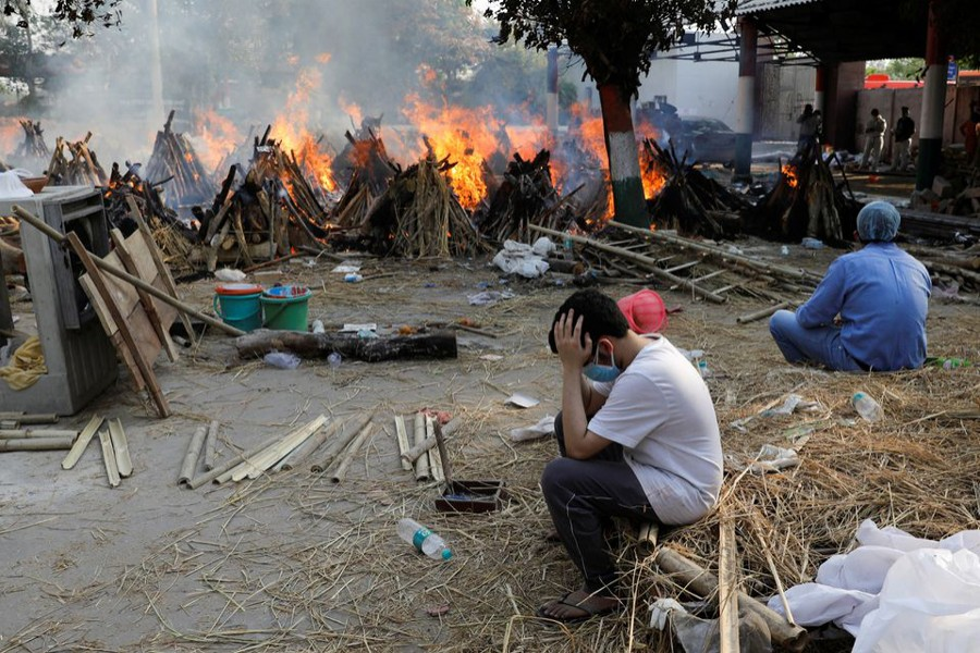 Family members sit next to the burning funeral pyres of those who died from the coronavirus disease (Covid-19), during a mass cremation, at a crematorium in New Delhi, India on April 26, 2021 — Reuters photo